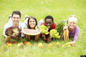Teenagers in the park with different fruits and vegetables.